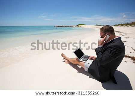 Businessman on the beach working with computer and speaking on phone - stock photo