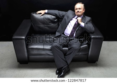 Businessman on the black couch in a full length image