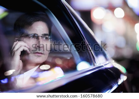 Businessman on the phone and looking out car window at night - stock photo
