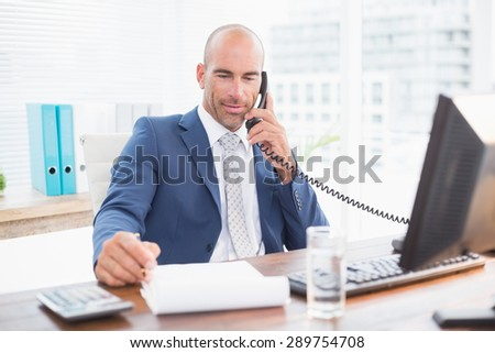 Businessman on the phone and writing notes in his office - stock photo