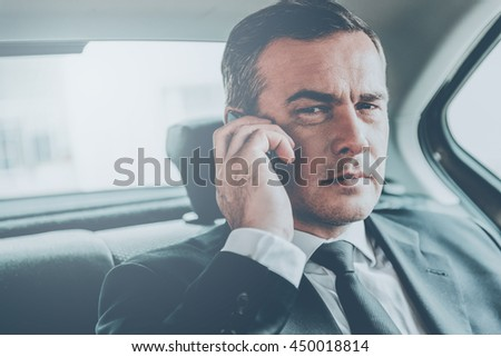 Businessman on the phone. Confident mature businessman talking on the mobile phone and looking away while sitting on the back seat of a car - stock photo