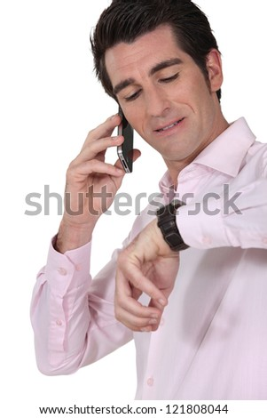 businessman on the phone consulting his watch - stock photo