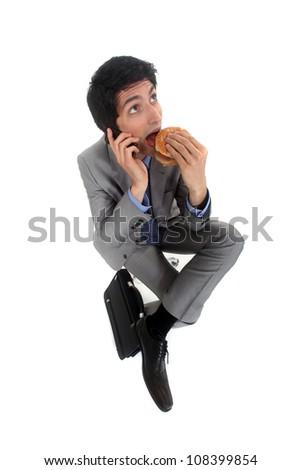 Businessman on the phone eating hamburger - stock photo