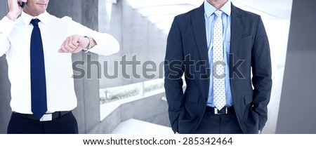 Businessman on the phone looking at his wrist watch against stylish modern home interior with staircase - stock photo