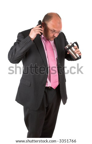 Businessman on the phone looking shocked because he has just spilled some of the coffee from his mug
