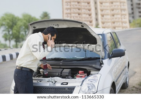 Businessman on the phone looking under the car hood - stock photo