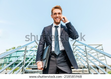 Businessman on the phone. Low angle view of confident young man in formalwear talking on the mobile phone and smiling while moving down by staircase