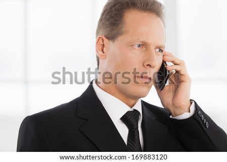 Businessman on the phone. Portrait of confident mature man in formalwear talking on the phone while standing near window