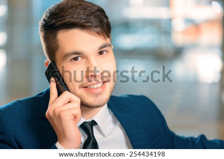 Businessman on the phone. Side view of handsome smiling businessman in formalwear talking over the mobile phone while sitting in the airport   - stock photo