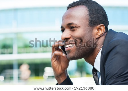 Businessman on the phone. Side view of handsome young African man in formal wear talking on the mobile phone and smiling while standing outdoors