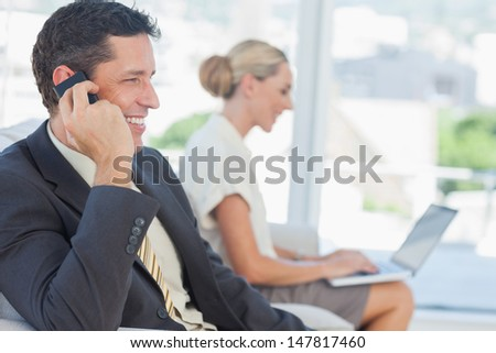 Businessman on the phone with his colleague working on computer in bright office - stock photo