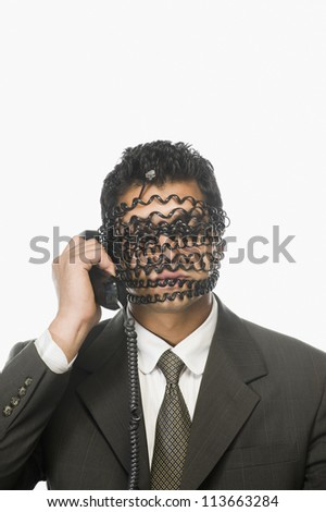 Businessman on the phone with his face covered by phone cord - stock photo