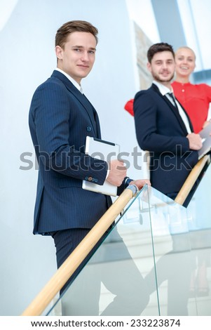 Businessman on the stairs. Confident young man holding tablet in hand and looking at the camera with a smile while his colleagues talking in the background. - stock photo