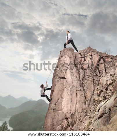 Businessman on the top of a rock helping an other businessman to climb it - stock photo