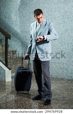Businessman on travel looking at his watch - stock photo