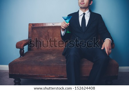 Businessman on vintage sofa drinking cocktail - stock photo