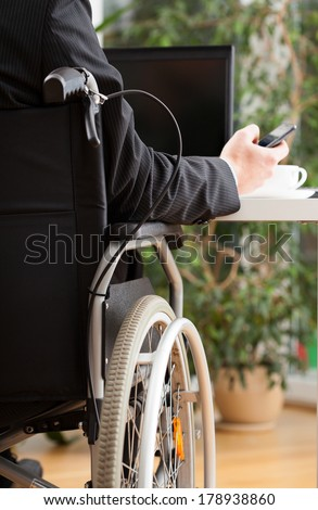 Businessman on wheelchair texting during his work in office - stock photo