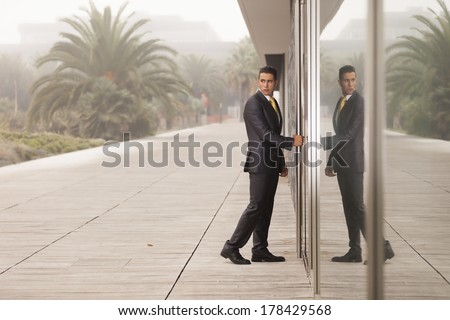 Businessman open the office door and looking back - stock photo