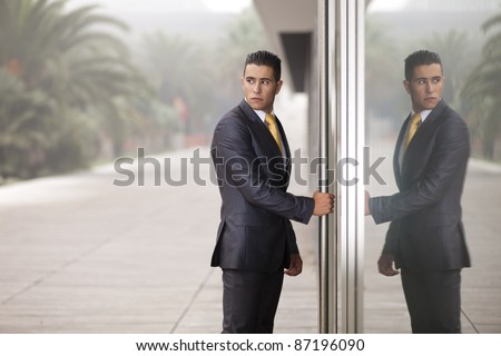 Businessman open the office door and looking back (with reflection on the glass door)