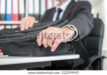 Businessman opening his laptop suitcase at the office