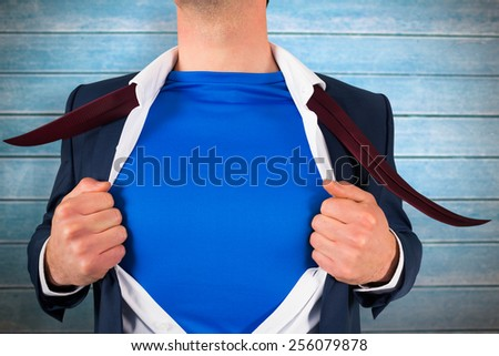 Businessman opening his shirt superhero style against wooden planks - stock photo