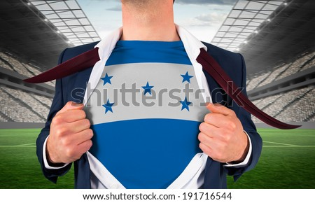 Businessman opening shirt to reveal honduras flag against vast football stadium with fans in white - stock photo