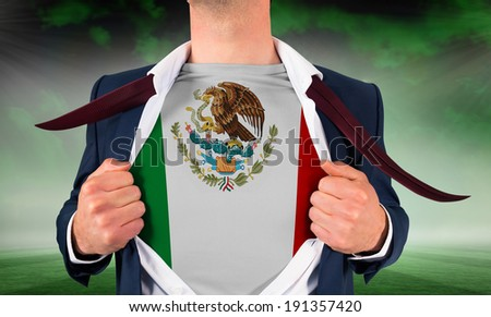Businessman opening shirt to reveal mexico flag against football pitch under green sky - stock photo