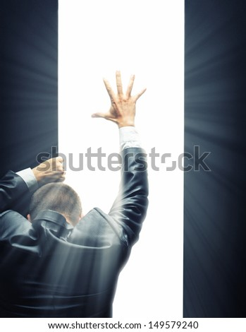 Businessman opening some gate and reaching hand to a bright light - stock photo