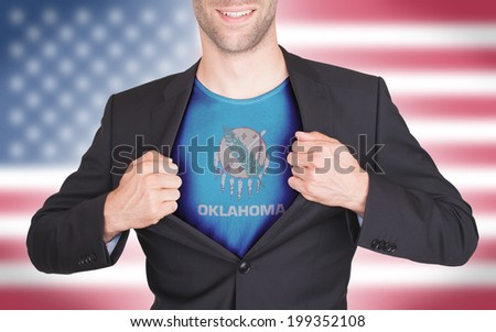 Businessman opening suit to reveal shirt with state flag (USA), Oklahoma - stock photo