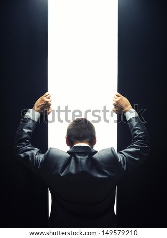 Businessman opening the gate to a bright light - stock photo