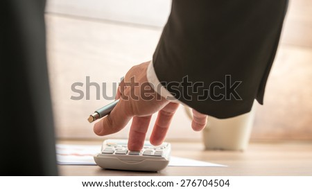 Businessman or accountant doing important financial calculation on a manual desk top calculator, low angle view between his arm and body of the paperwork. - stock photo