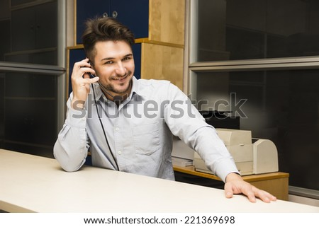 Businessman or customer (support) service man taking a call on his headset phone as he sits at a table in the office looking up to smile at the camera as he listens to the conversation - stock photo