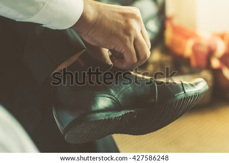 businessman or groom tied a shoelace on his black shoes. - stock photo