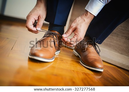 Businessman or groom tied a shoelace on his brown shoes. Shallow depth of field. - stock photo
