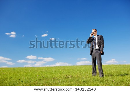 Businessman or manager using his mobile phone while standing in a sunny green field under a beautiful sunny blue sky with copyspace