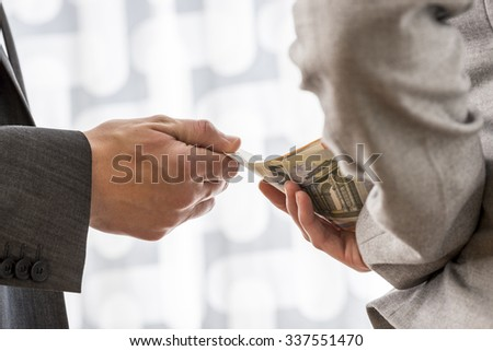 Businessman or politician taking bribe from a female colleague handing him Euro money from behind her back. Conceptual of corruption and bribery. - stock photo