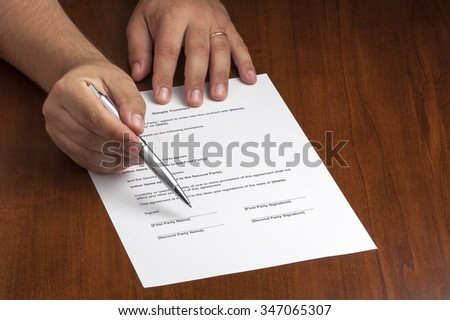 businessman or salesman hand holding silver ballpoint pointing on contract where customer have to sign