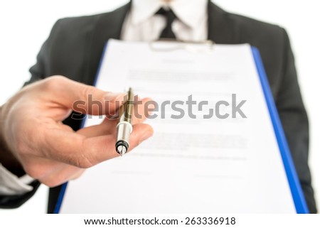 Businessman or salesman handing over a contract attached to a clipboard for signature offering a ballpoint pen in his hand with focus to the pen. - stock photo