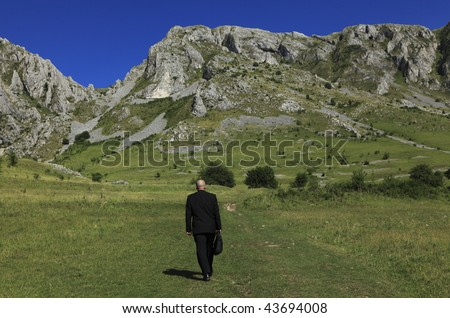 Businessman oudoors walking through a big mountain.The main focus is on the rocks,the man is slighty out of focus.