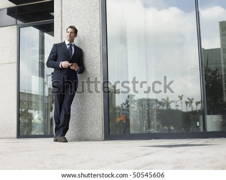 Businessman outside office building - stock photo