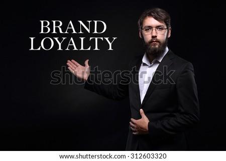 "Businessman over black background presenting ""Brand loyalty"" - stock photo"