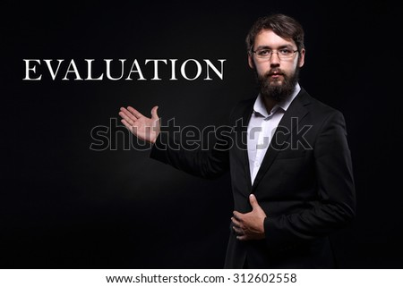 "Businessman over black background presenting ""Evaluation"" - stock photo"