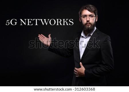 "Businessman over black background presenting ""5G networks"" - stock photo"