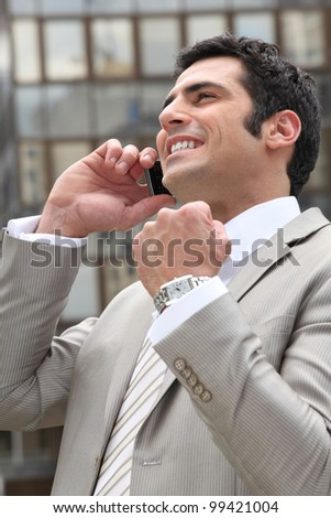 Businessman overjoyed with his phone call - stock photo