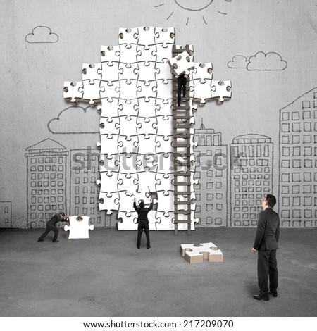 businessman oversee teamwork for puzzles in arrow shape on doodles wall - stock photo