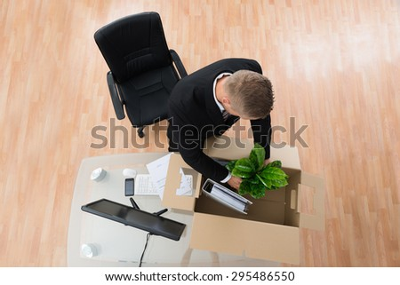 Businessman Packing Belongings In Cardboard Box At The Desk - stock photo