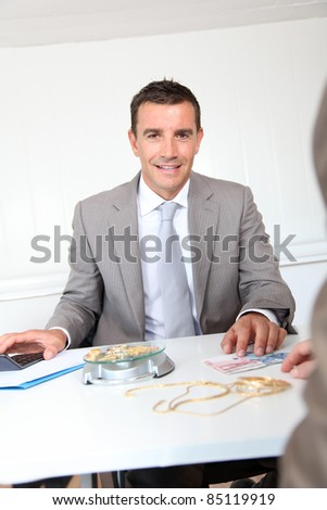 Businessman paying for golden jewels