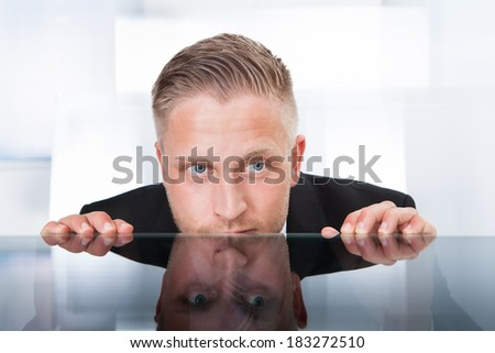 Businessman peering furtively over the top of his desk as he spies on a colleague or tries to remain out of the firing line to avoid any blame for a problem  isolated on white - stock photo