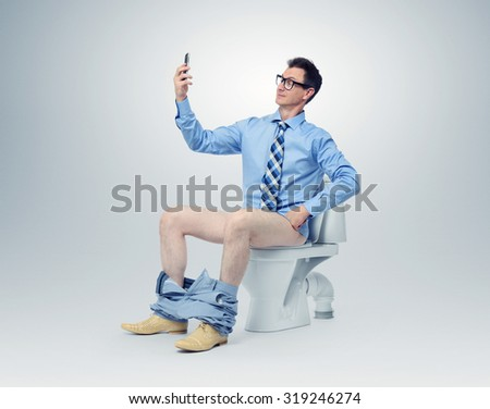Businessman photographing himself in the toilet - stock photo