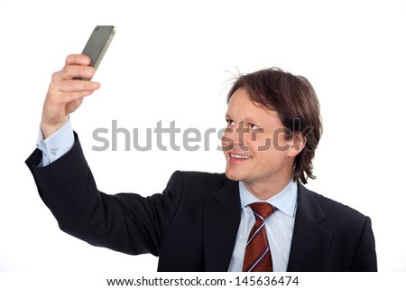 Businessman photographing himself with his mobile phone holding it up in the air and smiling into it, on white - stock photo